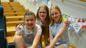 Tre flickor sitter på en trappa och håller om varandra