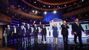 Kandidaterna står på rad och vinkar till publiken efter debatten.