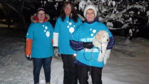 tre damer, Mirja Koponen, Synnöve Lindholm och Karin Svahnström med vita hunden Albert i famnen poserar i ett snöigt, vintrigt landskap en kväll i november. De tre damerna har turkosa Gåkampen t-skjortor ovanpå sina ytterrockar.