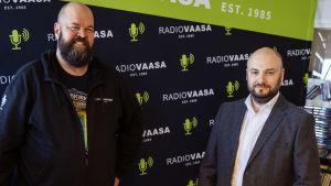 Två manspersoner står tillsammans och ser in i kameran, i bakgrunden syns Radio Vasas lokaler.