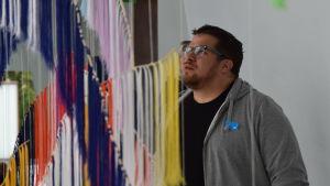 Närbild på Oscar Ortiz-Nieminen då han ser på Outi Pieskis verk.