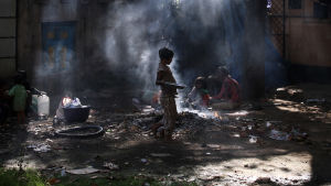 Hemlösa indier bränner skräp på en soptipp i Bombay.