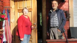 En äldre kvinna och äldre man står framför en rödmålad stockstuga. De ser in i kameran och kvinnan öppnar dörren till huset.