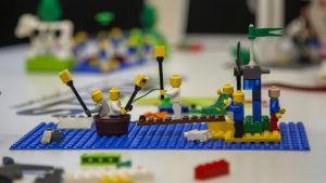 Legogubbar åker i en tunna framför en legoö med brygga.