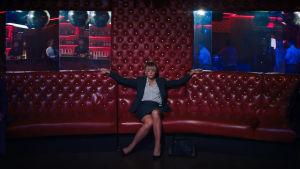 Cassandra (Carey Mulligan) sitter avslocknad i en soffa på en nattklubb.
