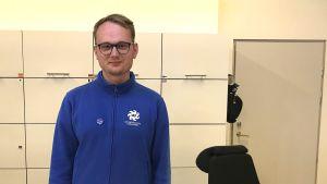 Aslak Djupsjö iförd en blå tröja står framför en rad med vita skåpdörrar.