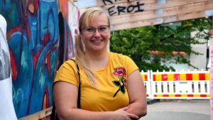 Kvinna med blont hår och glasögon ler.