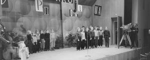 """Yleisradion televisiotoiminnan ensimmäinen julkinen televisioitu lähetys """"Pikkujoulu on taas"""" 30.11.1957 Ruotsinkieliseltä kauppakorkeakoululta Helsingistä. Lapsikuoro """"Tontut"""" laulaa, Onni Gideonin yhtye vasemmalla."""
