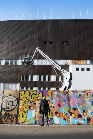 MOT:n haastattelema Ilir seisoo Olympiastadionin työmaan vieressä.