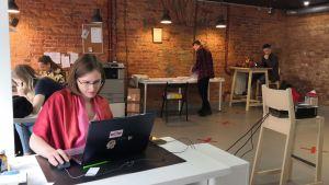 En kvinna sitter vid en dator i ett öppet kontorslandskap med röd tegelvägg.