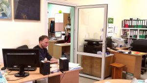 En man sitter i ett litet rum bakom ett skrivbord.