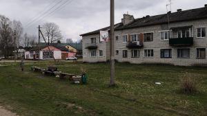 En grå tegelbyggnad. Framför byggnaden står en kvinna