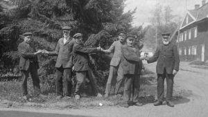 """Flera män leker leken """"dra fingerkrok"""" på en väg. Bilden är tagen 1929 i Strömfors bruk."""