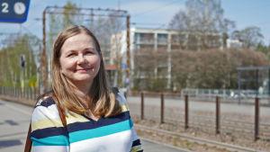 Tiina Ignatius står vid järnvägsspår i solsken.