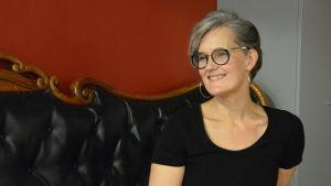 Kvinna med glasögon sitter på en soffa med en röd vägg bakom sig.