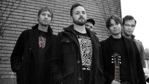 Bandet Pastis poserar utomhus med gitarr 2019.