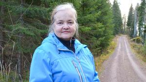 En kvinna vid en skogsväg.