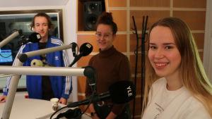 Tre ungdomar i en radiostudio med mikrofoner.