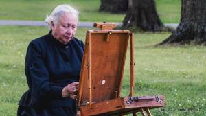 Kvinna i vitt hår och svart hellång klänning sitter och målar vid ett staffli i en park.