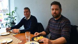 Två män sitter vid ett bord med mat framför sig.