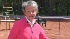 En kvinna står på ett tennisplan. Ser in i kameran. Spelar inte.