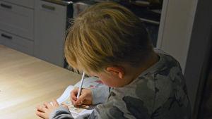 Ett barn ritar i en bok.