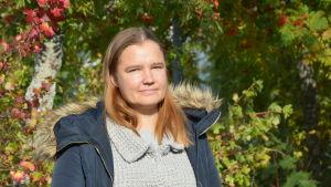Lotta Björklund står bredvid buskar vars blad hunnit bli lite röda av höstkylan.