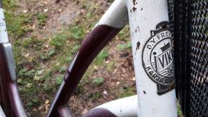 Ett märke på en gammal cykel där det står O.Y.From och Karjaa.