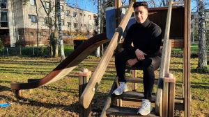 En ung man sitter på en trappa upp till en rutschkana. Han tittar mot kameran och ler.