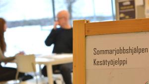 En skylt där det står Sommarjobbshjälpen. I bakgrunden skymtar två personer vid ett bord.