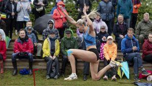 Kristiina Mäkelä i luften vid sandgropen framför publik.