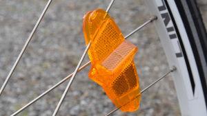Närbild av ett orange reflex i plast fastsatt på ekrarna i ett cykelhjul.