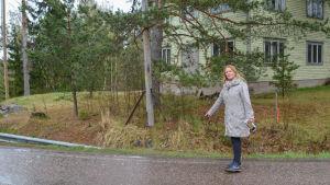 Kvinna pekar på vägkanten en regning majdag