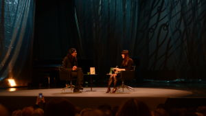 En man och en kvinna samtalar på scen.