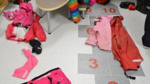 Regnkläder och ytterkläder i en daghemstambur.