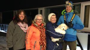 Synnöve Lindholm, Mirja Koponen, Karin Svahnström med hunden Albert i famnen och idrottsinstruktör Heikki Kiili poserar utanför Solvalla Arenan en vintrig kväll i november.