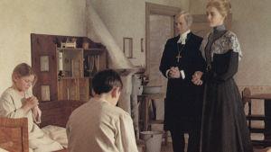 Fanny och Alexander ber aftonbön under uppsikt av biskopen och sin mor.