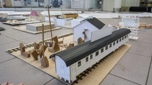 En miniatyrmodell av en tågvagn på en räls och en byggnad.