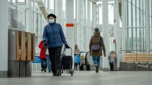 Människor på metrostationen i Nordsjö, Helsingfors. I förgrunden har en äldre kvinna munskydd.