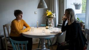 Emma och Susanne sitter mittemot varann kring ett matbord.