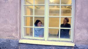 Maikku Huovila och Katja Sågbom sedda genom ett rutfönster.