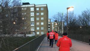 En grupp mänskor i röda jackor går på trottoaren i ett bostadsområde.