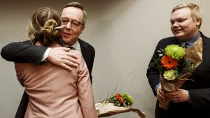 Katri Kulmuni är fotograferad bakifrån när hon får en kram av Mika Lintilä.
