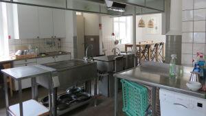 Ett storkök med mycket utrustning i rostfritt stål. Längst bak ett högt långsmalt, litet bord med några höga barstolar.