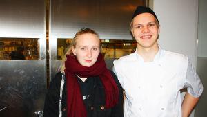 En flick och en pojke iklädd kockmössa som står bredvid varandra och ler.