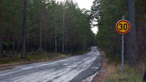 En grusväg omringad av skog. Vid vägkanten syns en hastighetsbegräsningsskylt där det står 30.