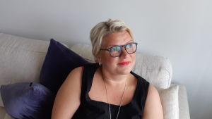 Mela, Mikaela Nyholm i sitt hem i soffan, där hon ser ut på björkarna. Maj 2019