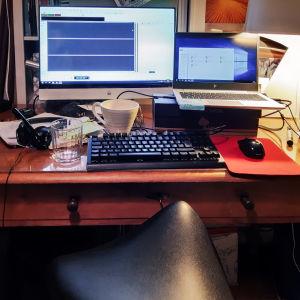 Gammalt skrivbord i trä med bärbar dator, mikrofon och hörlurar, datorskärm påslagen