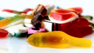 En hög med olika färgs godisar ligger på en vit yta.