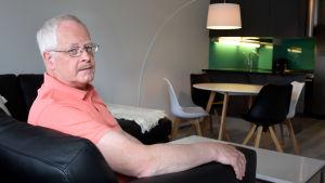 Berndt Huldin sitter i en svart lädersoffa. I bakgrunden skymtar ett köksbord och ett kök.